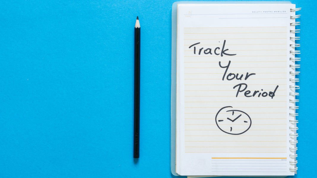 Pencil and Notebook on blue background saying track your period